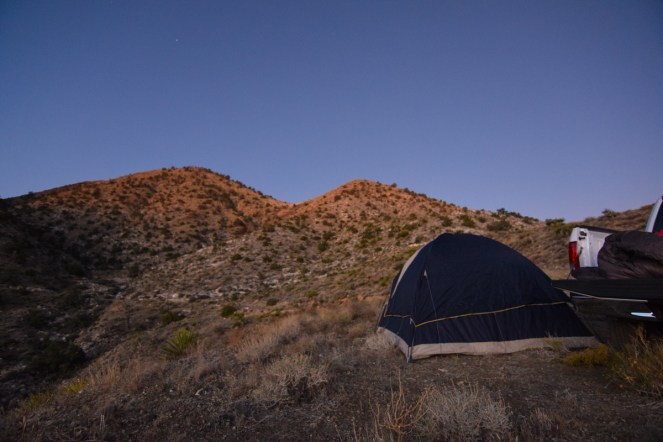 The tops of scrub covered hills start to glow with the first light of sunrise in the Mojave Desert. A tent and open truck bed sit in the foreground.