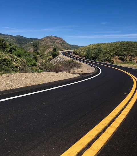 An empty blacktop back road swerves through rolling hills in California