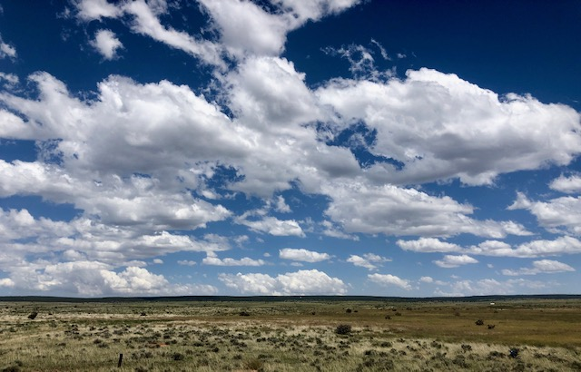 A brilliant blue sky filled with fluffy white clouds expands over the flat plains of New Mexico