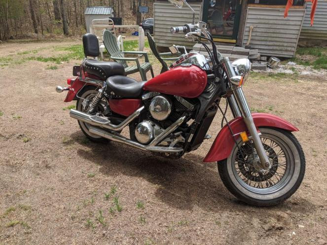 Bright red Kawasaki Vulcan Classic motorcycle, photographed showing off the exhaust pipes