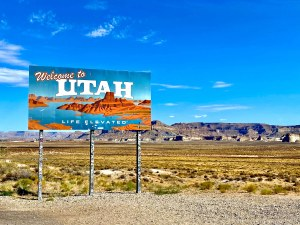 Utah border sign with rock formations in the background