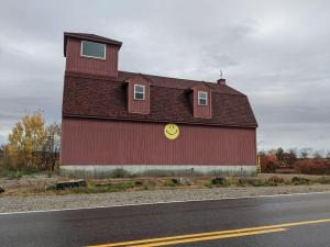 A large red barn with a yellow smiley face painted on the side sits by the road in rural Maine