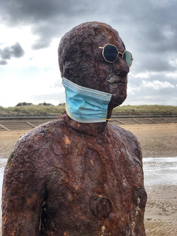 Iron men at Anthony Gormley's Another Place at Crosby Beach, England wearing surgical masks