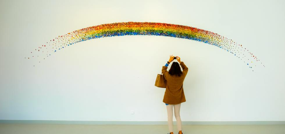Woman in brown jacket taking picture of a rainbow mural