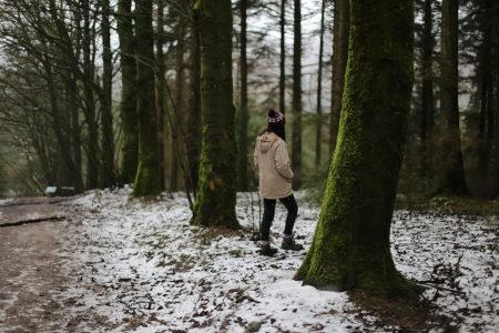 young women in winter clothes steps into snowy woodland