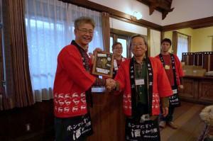 クイズ大会の優勝者に前回のチャンピオンから賞品目録の贈呈です