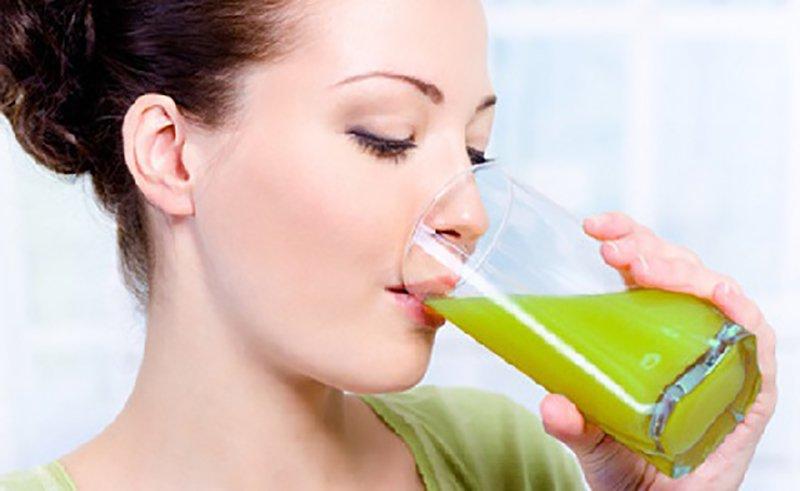 девушка пьет зеленый сок, сжигающий жиры