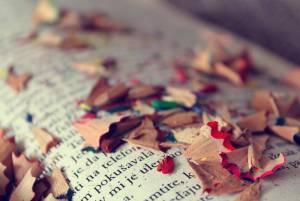 Libro abierto con virutas de sacar punta a lápices de colores