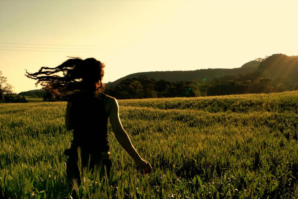 mujer de espaldas corriendo por campo