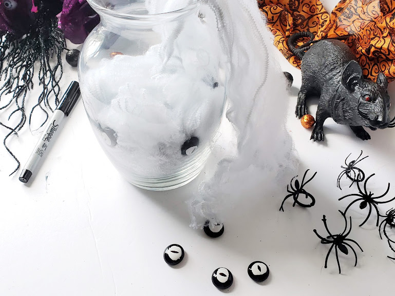 creating a halloween dollar store vase, adding the spider web filling