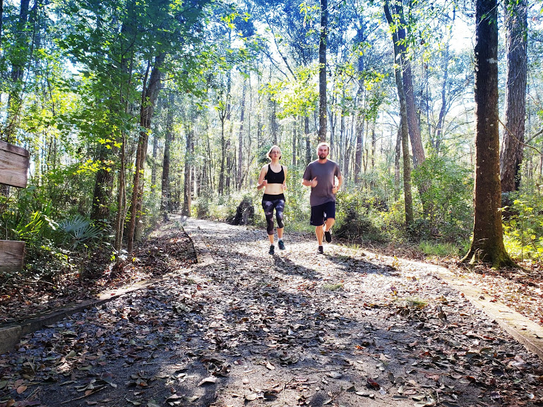 Two people running in the woods