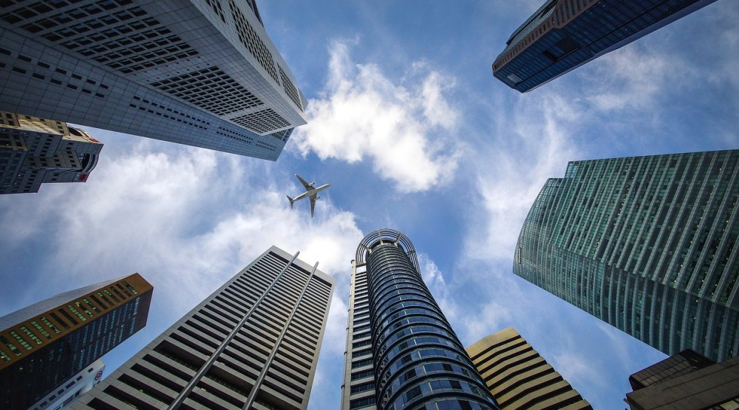 Plane Flying over Buildings - How to Find the Best Flight Deals for Black Friday with Skyscanner