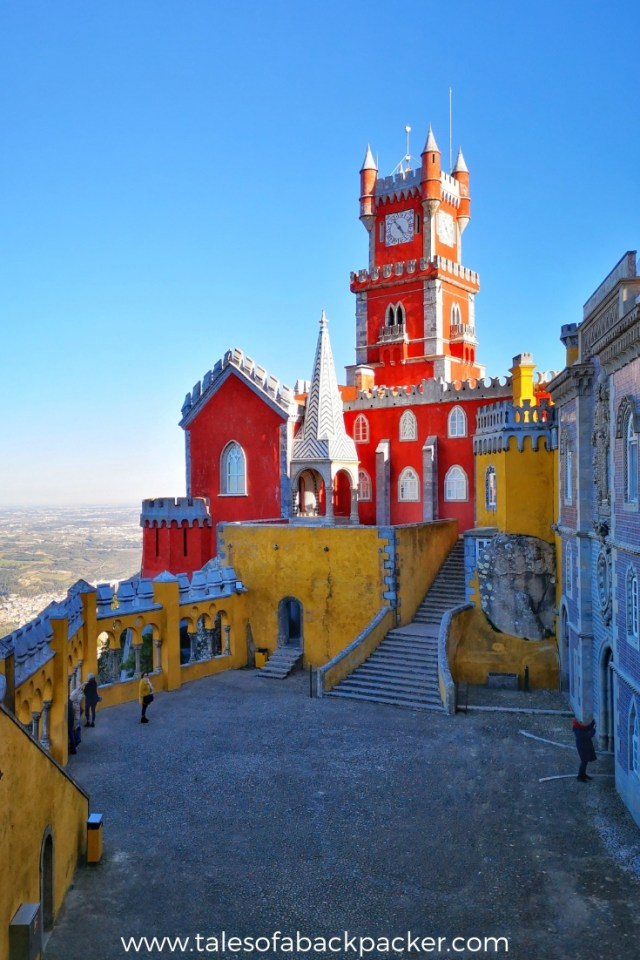El Palacio da Pena is the most famous castle in Sintra, and the one you'll see on all the Portugal guide book photos.  The brightly coloured red and yellow towers are visible from all around Sintra, as this castle is high on the hillside and the gardens include the highest point in Sintra.  The castle is a dream for Instagram fans and photographers, so take your time to explore the terraces and gardens of Pena Park to find the best views of Pena Palace, you won't regret it – and you don't even need to pay full price for the Pena Palace tickets!  Here are all my tips for visiting Pena Palace and Gardens. #Portugal #Sintra #PenaPalace #Photography #Castle