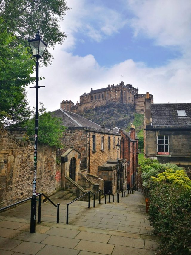 The Vennel Viewpoint of Edinburgh Castle - Narrow street with steps leading down with the Castle in the background