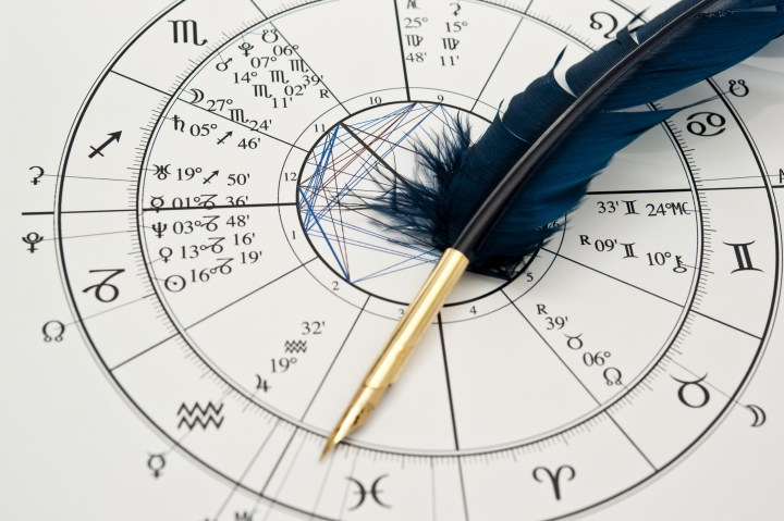 quill pen in form ob blue feather lying on horoscope and zodiac signs like astrology concept