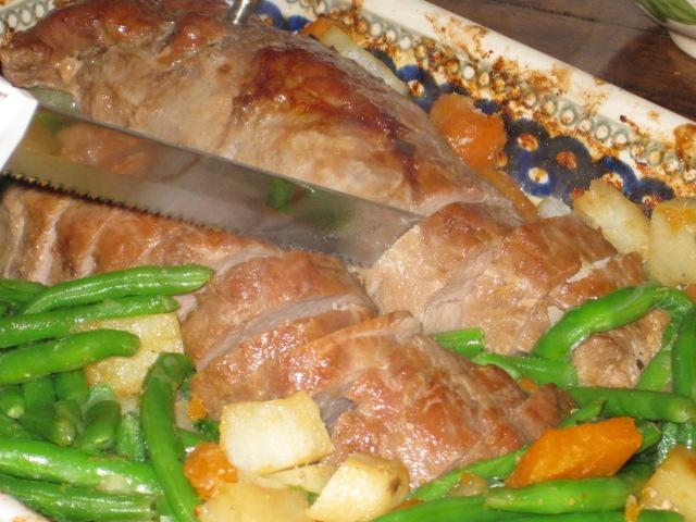 Stepmom slicing terriyaki pork tenderloin (flanked by sweet potatoes, white potatoes, carrots, and green beans)