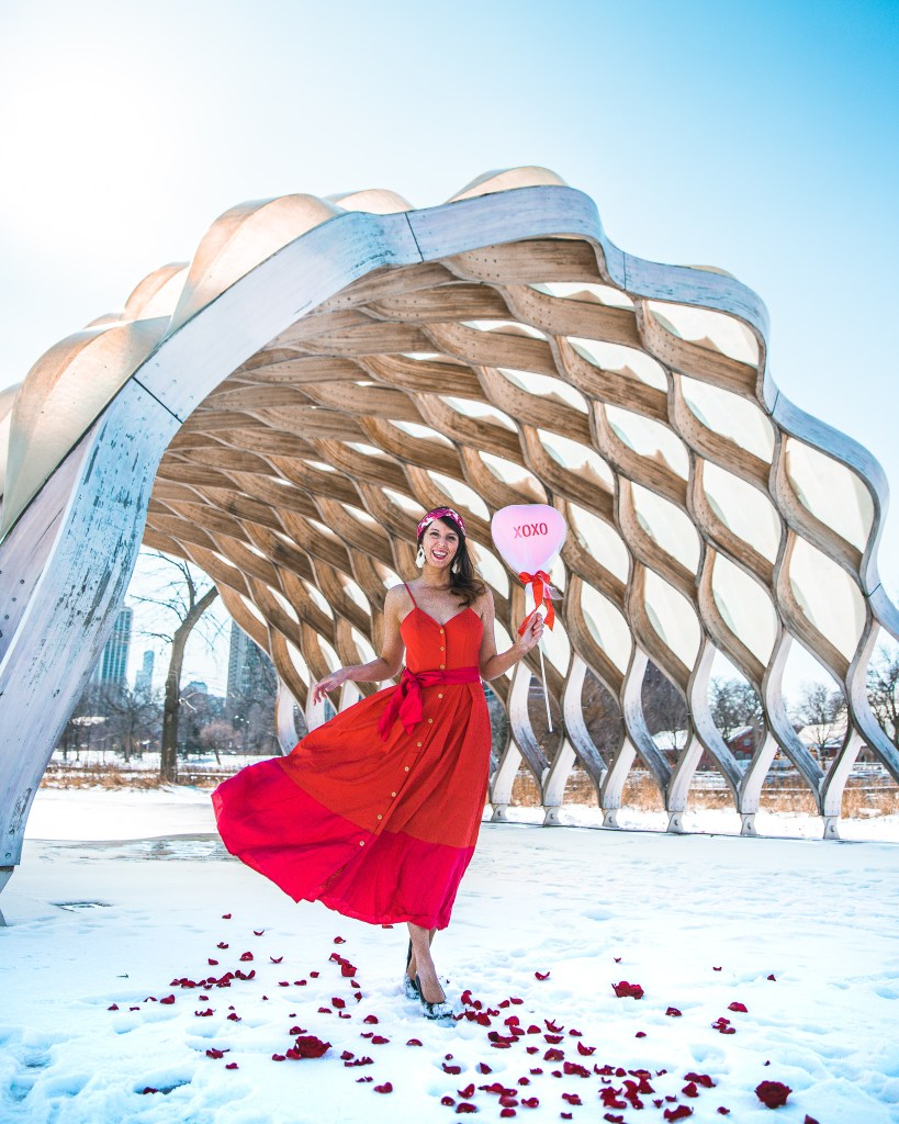 Woman holding a heart balloon and wearing a red dress in front of the honeycomb in Lincoln Park, Chicago.