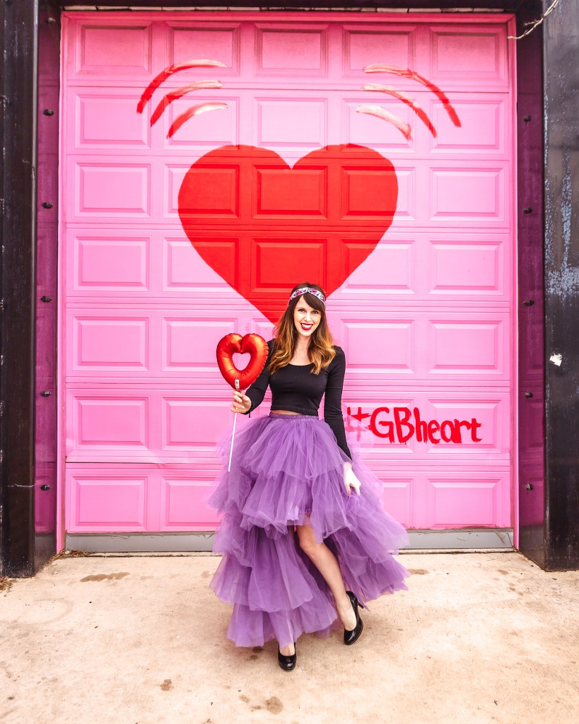 Heart Emoji Mural with woman who is holding a heart balloon and wearing a tulle skirt.