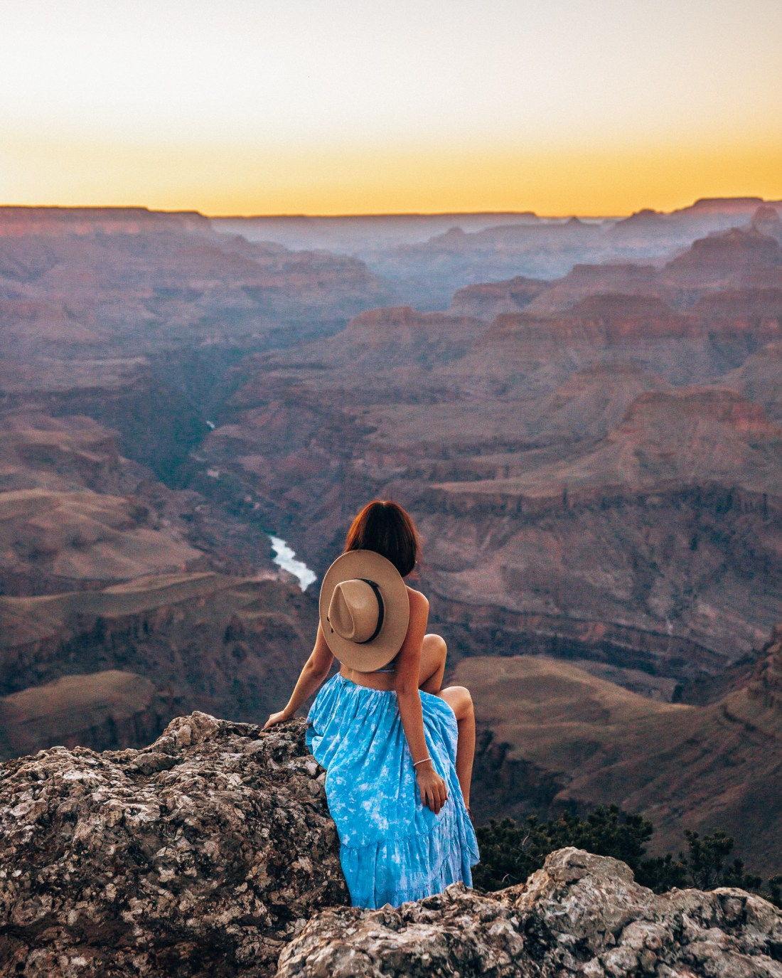 Woman sitting on a cliff watching the sunset at Lipan Point