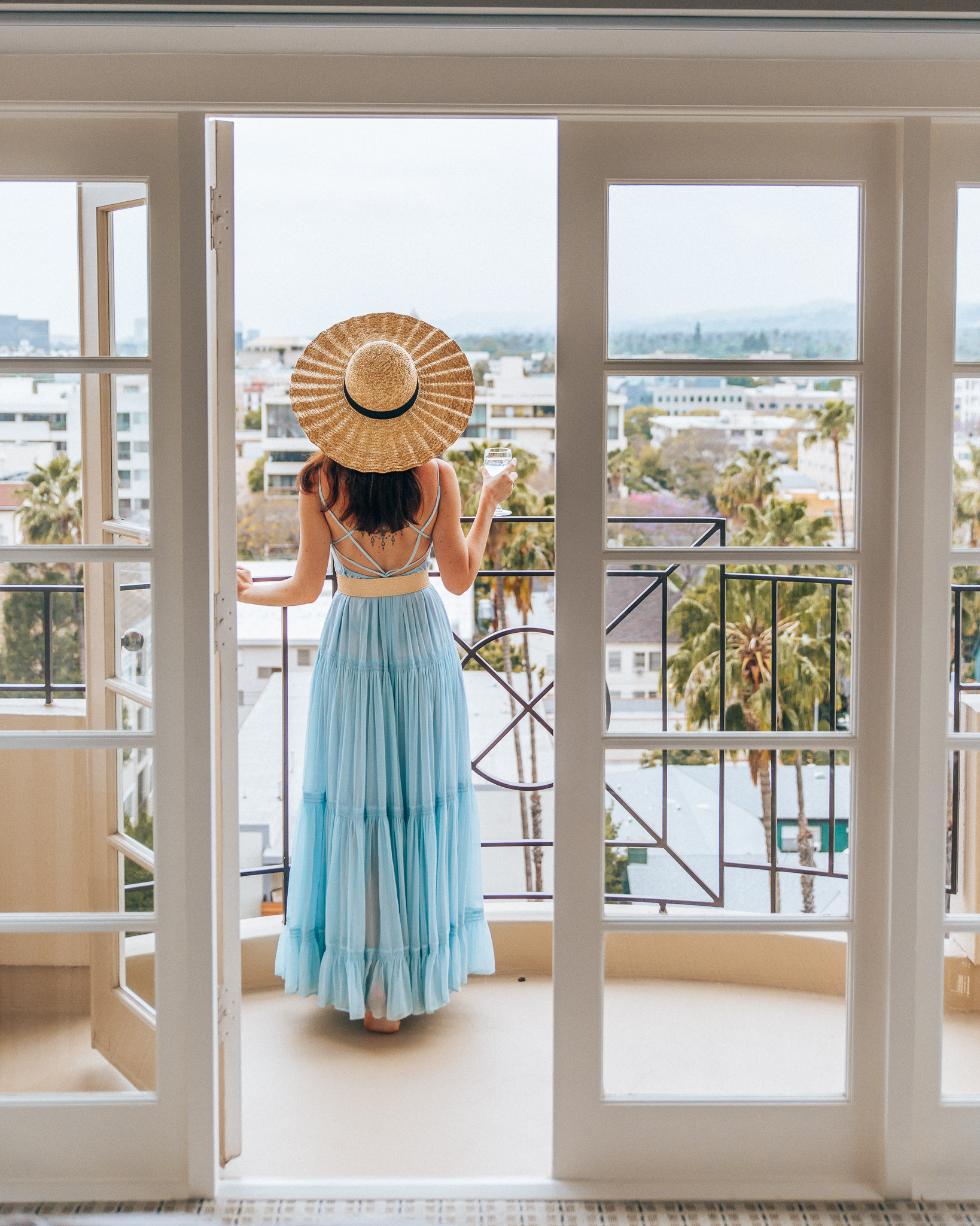 Woman in long blue dress and a hat at the Four Seasons Beverly Hills Balcony Room view