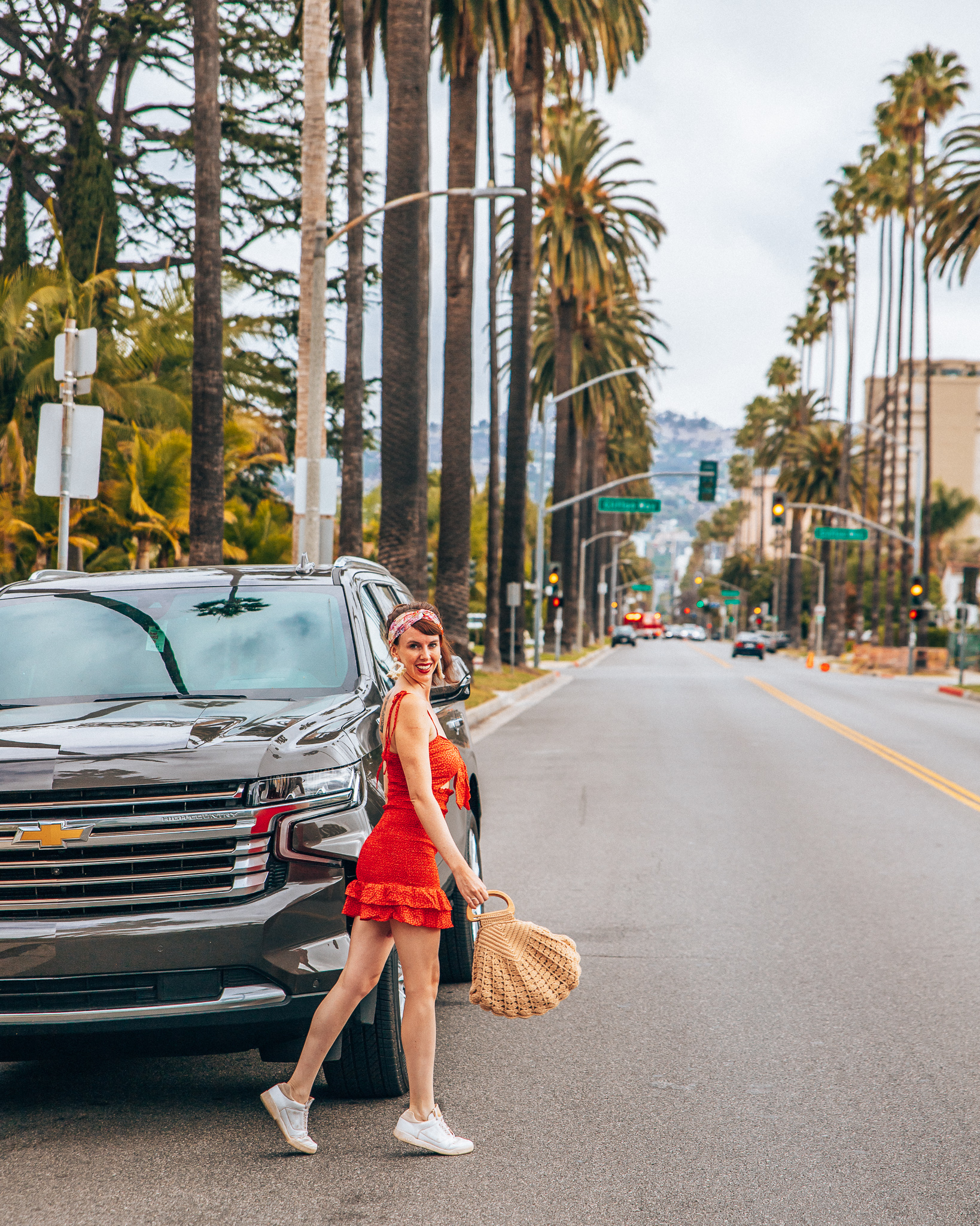 Girl in red mini dress with a purse walking in front of a Chevrolet Tahoe