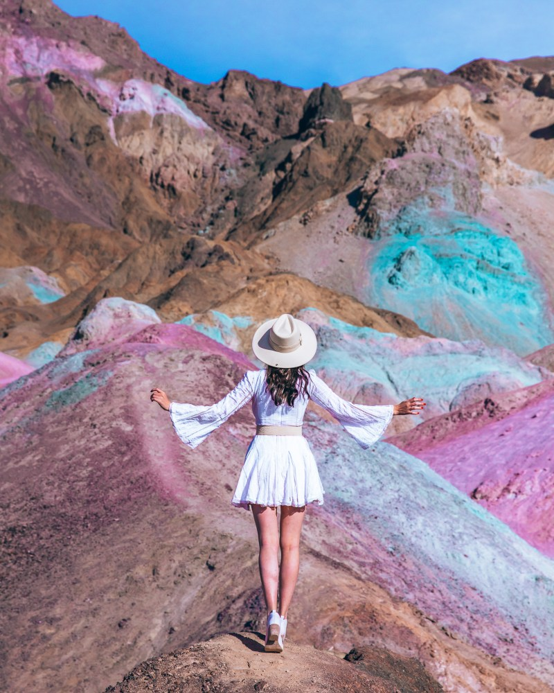 Woman in white midi dress looking at Artists Palette Death Valley National Park