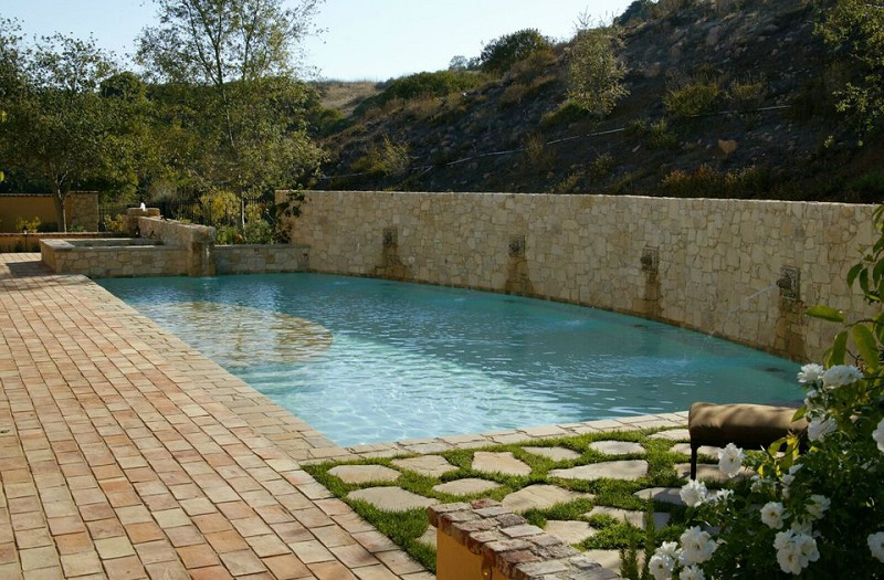Mediterranean Pool With Stone Wall