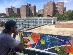 1.Erik Burke, mural artist, taking a step back to view his completed mural, Harlem