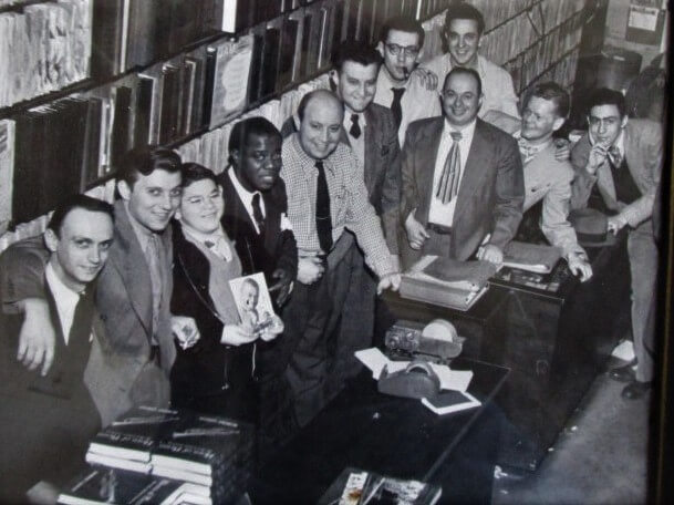 """1947, Eugene Kramer (first row, last, rear). Matt Gabler founder of the famous Commodore Music Shop at 136 East 42 Street greets Louis Armstrong at an autographing session on behalf of Robert Griffin's """"Horns of Plenty."""" Arrayed around Armstrong and Gabler are members of the store's staff, including Jack Crystal, Billy Crystal's father. From NY Times asks for help with """"A Jackie Robinson Mystery."""" Well, Eugene Kramer was there. (Almost)"""