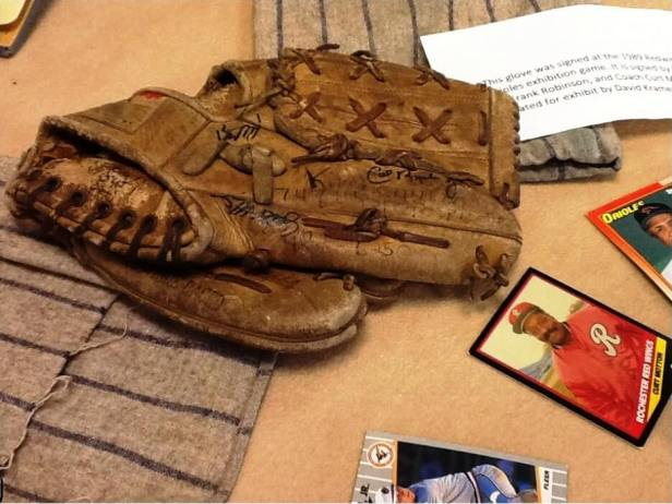 """Exhibit note: """"This glove was signed at the 1989 Redwings [sic] vs. Orioles exhibition game. It is signed by Cal Ripken Jr., Frank Robinson, and Coach Curt Motton. Donated for exhibit by David Kramer.]"""