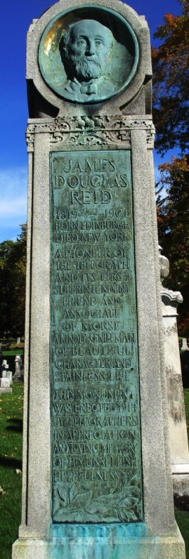 """The James Reid monument in Mount Hope Cemetery is a square column set on three graduated marble steps. Two of the four faces of the top section are visible in this photograph. One has Reid's birth year, 1819, enclosed in a wreath. The second contains a bronze portrait plaque of Mr. Reid. The bronze tablet set into the support column reads, """"James Douglas Reid, 1819-1901. Born Edinburgh, died New York. A pioneer of the telegraph and its first superintendent. Friend and associate of Morse. A kindly gentleman of beautiful character and stainless life. This monument was erected 1914 by telegraphers in appreciation and loving memory of his unselfish helpfulness"""". From the Monroe County Library website"""