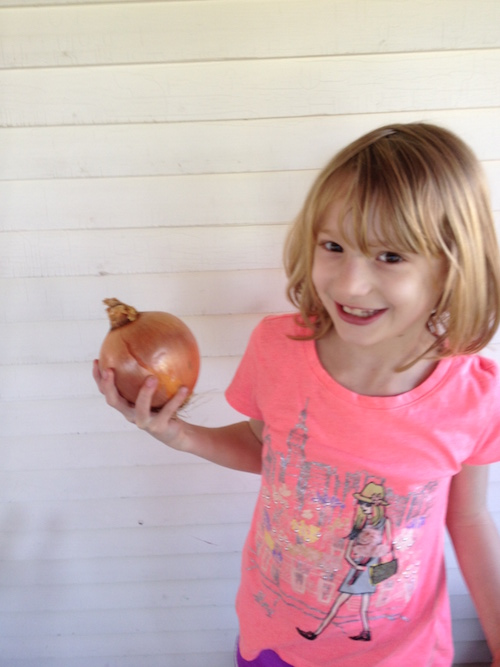 Tabitha holding a large onion