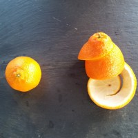 Two tangerines—one is intact, and the other has its peel cut into a spiral