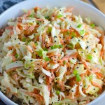 Sesame Asian Coleslaw in a bowl! It has cabbage, carrots, scallions, and sesame seeds in a creamy dressing with mayonnaise. vinegar, soy sauce, and Sesame Oil. It really is a sidekick that can go with anything!