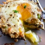 Portabella Mushroom Egg Nests on plate with bite cut out and runny yoke and fork on plate. Portabella mushrooms are filled with garlic, scallion, breadcrumb & Manchego cheese stuffing!  Then an egg is baked nestled in the center of all of this goodness.