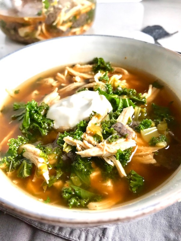 Chicken Tortilla Soup with sour cream on top in bowl on counter