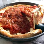 Spatula lifting slice Chicago Style pizza with tomatoes on top.This Chicago Style Pizza is a lighter and healthier version, but still AMAZING! It still has all of the gooey mozzarella cheese, but uses homemade turkey Italian Sausage, that's so delicious!