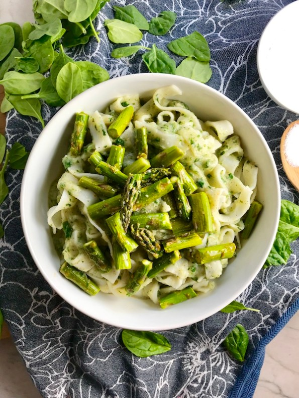 Pasta with spinach, asparagus, cauliflower sauce in bowl on blue towel