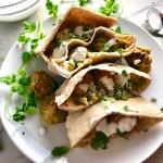 Pitas on plate stuffed with meatballs and hummus with yogurt sauce on top and parsley