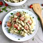 Noodles with cauliflower cream sauce, sausage, and tomatoes on white plate on counter with tomatoes, parsley, and spoon on counter