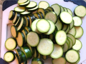 Raw slices of Zucchini on cutting board.