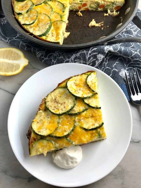 Vegetable Frittata with Lemon Crema is an easy weeknight dinner, quick breakfast, or weekend brunch recipe! This Vegetable Frittata is thick and hearty with lots of flavors and textures from the veggies, but is also light and creamy from the eggs and cheese. It's loaded with healthy veggies, is gluten free, and super EASY to make and to clean up after.