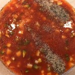Roasted Red Pepper Gazpacho recipe in a bowl with salt and pepper on top before mixing. The other ingredients are roasted red pepper, green pepper, cucumber, garlic and scallions.
