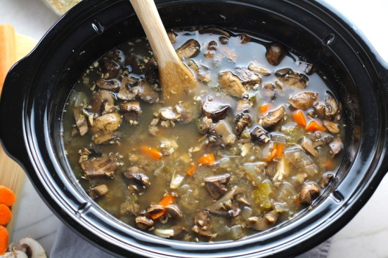 Cooked chicken and mushroom soup in slow cooker with wood spoon. This Slow Cooker Chicken and Mushroom Soup is warm, hearty, comforting, earthy, and just devine. The mix of blended and chunky mushrooms with carrots, onions, celery, shredded chicken, and herbs gives you a perfect bite every time.