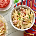 Close up of Mexican Pasta Salad in white bowl on counter with second bowl in upper left corner and tomato half on plate. This Creamy Mexican Pasta Salad has Sun Dried Tomatoes, Corn, Fresh Diced Tomatoes, Cilantro, and smoky Mexican spices. The dressing is creamy and smoky with lots of depth and a hint of sweetness from the Sun Dried Tomatoes that are blended in. Terrific as a side or mix in some chicken or beef and call it a meal!