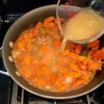 Chicken Broth being poured over carrots and onions in skillet. Smothered Pork Chop Casserole is a true midwestern comfort dish with layers of vegetables and meaty pork chops smothered in a creamy sauce and cheese.  The pork chops in this delicious casserole are left whole so that you get an entire portion dripping in goodness in one scoop.