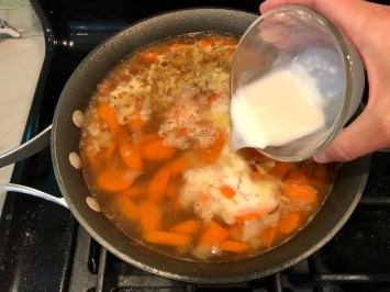Cornstarch slurry being poured over broth with carrots and onions. Smothered Pork Chop Casserole is a true midwestern comfort dish with layers of vegetables and meaty pork chops smothered in a creamy sauce and cheese.  The pork chops in this delicious casserole are left whole so that you get an entire portion dripping in goodness in one scoop.