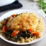 Pork Chop with cheese melted on top over carrots and kale on top of quinoa on plate on counter with casserole dish in background. Smothered Pork Chop Casserole is a true midwestern comfort dish with layers of vegetables and meaty pork chops smothered in a creamy sauce and cheese.  The pork chops in this delicious casserole are left whole so that you get an entire portion dripping in goodness in one scoop.
