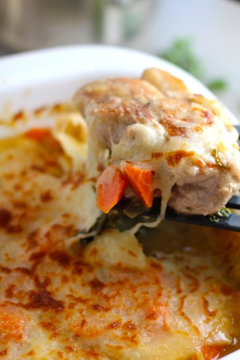 spatula lifting pork chop and carrots with cheese pulling. Smothered Pork Chop Casserole is a true midwestern comfort dish with layers of vegetables and meaty pork chops smothered in a creamy sauce and cheese.  The pork chops in this delicious casserole are left whole so that you get an entire portion dripping in goodness in one scoop.