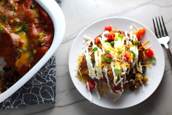 Piece of Taco Casserole on a white plate with sour cream drizzled on top with diced tomato and scallion. Casserole dish to the left on counter. This Taco Casserole has corn tortillas layered with browned ground chicken seasoned with smokey mexican spices, black beans, tomatoes, and cheese, and then more cheese.